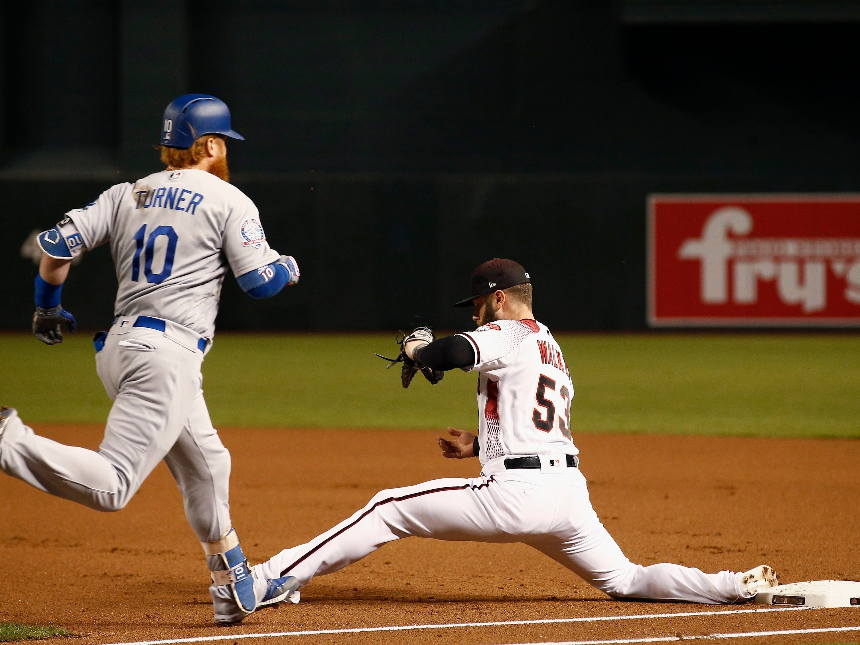 Arizona Diamondbacks first baseman Christian Walker (53) scoops up a low throw to get out Los Angeles Dodgers' Justin Turner (10) at first during the first inning of a baseball game, Monday, Sept. 24, 2018, in Phoenix. (AP Photo/Ross D. Franklin)