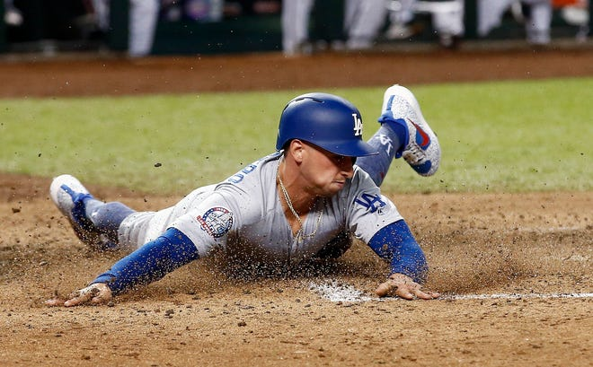 Los Angeles Dodgers' Tim Locastro (70) slides across home plate to score a run against the Arizona Diamondbacks during the seventh inning of a baseball game, Monday, Sept. 24, 2018, in Phoenix.
