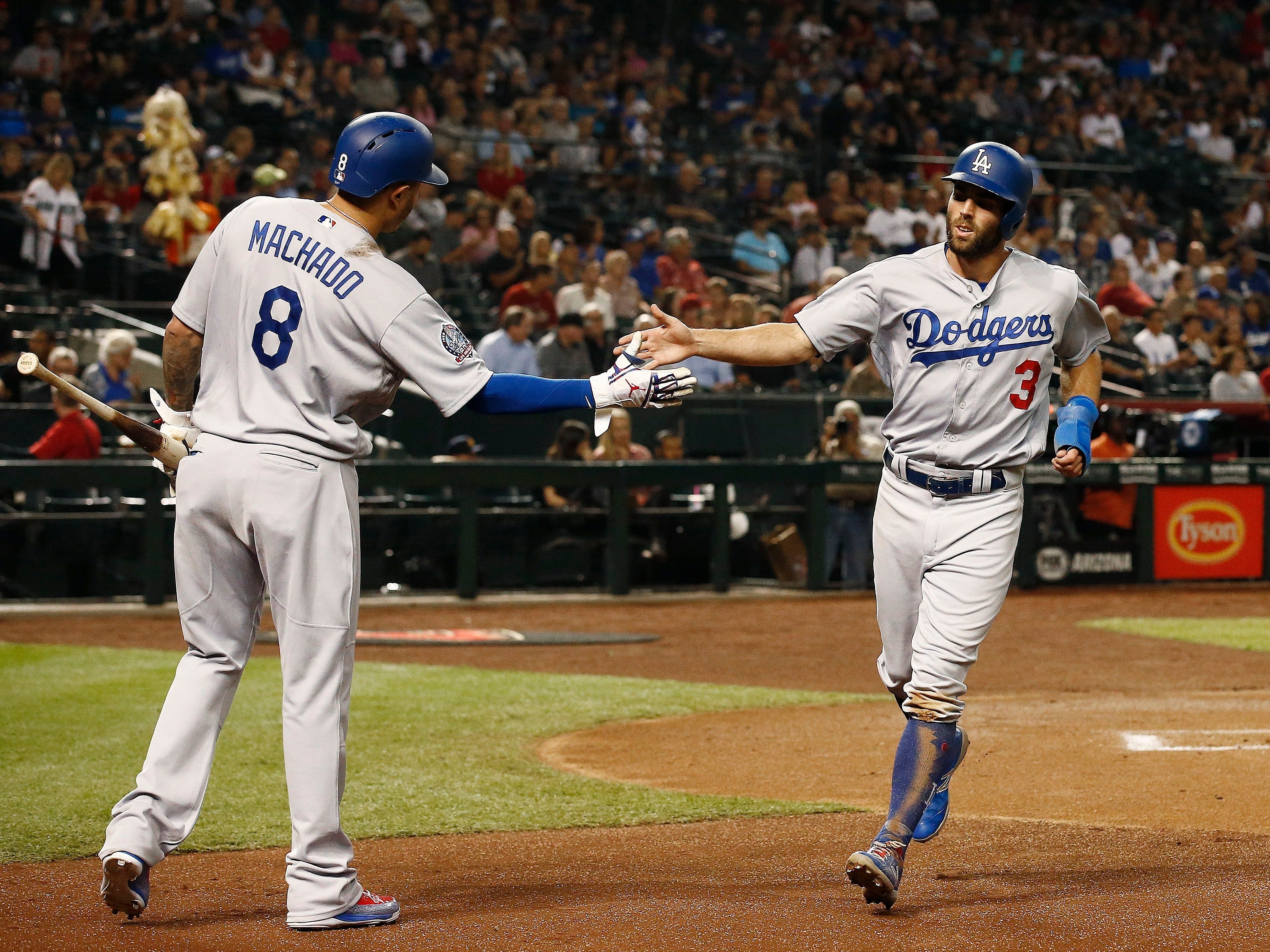 Los Angeles Dodgers' Chris Taylor (3) celebrates his run scored against the Arizona Diamondbacks with Manny Machado (8) during the first inning of a baseball game, Monday, Sept. 24, 2018, in Phoenix. (AP Photo/Ross D. Franklin)