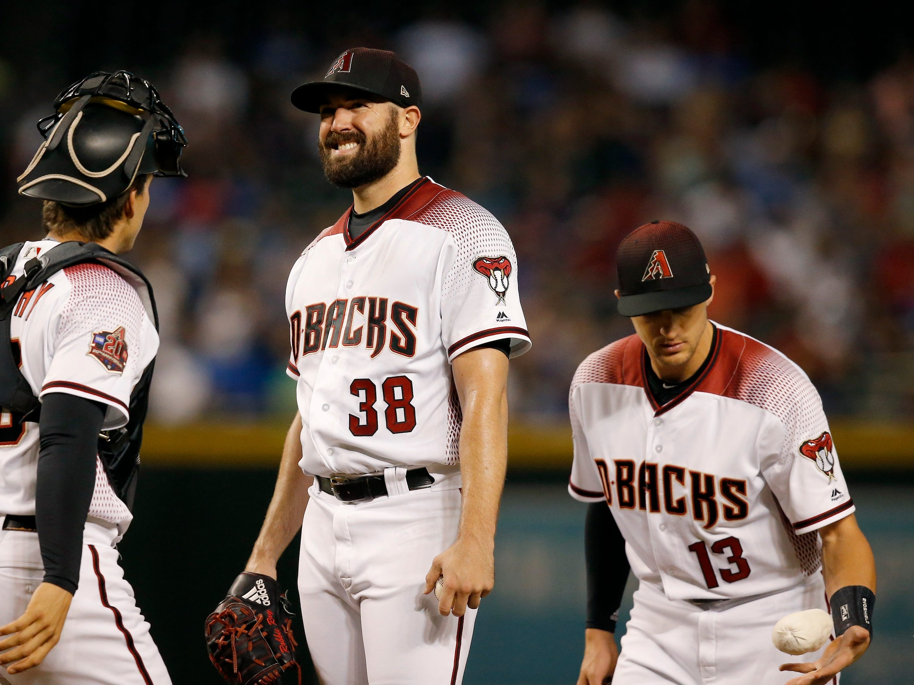 Arizona Diamondbacks starting pitcher Robbie Ray (38) gets a visit from catcher John Ryan Murphy, left, and shortstop Nick Ahmed (13) during the first inning of a baseball game against the Los Angeles Dodgers, Monday, Sept. 24, 2018, in Phoenix. (AP Photo/Ross D. Franklin)