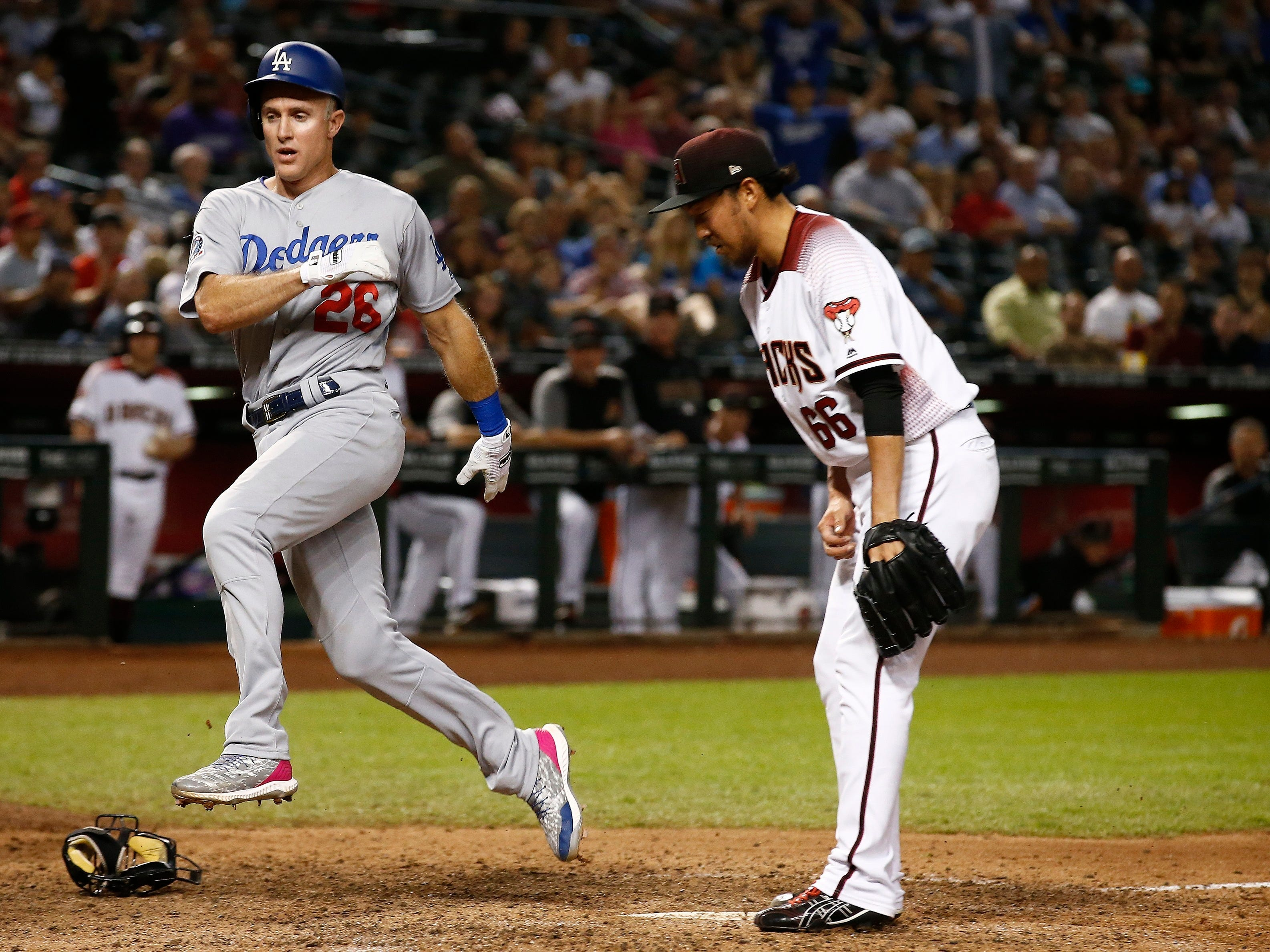 Los Angeles Dodgers' Chase Utley (26) scores a run on a wild pitch by Arizona Diamondbacks relief pitcher Yoshihisa Hirano (66), of Japan, during the ninth inning of a baseball game, Monday, Sept. 24, 2018, in Phoenix. The Dodgers defeated the Diamondbacks 7-4. (AP Photo/Ross D. Franklin)