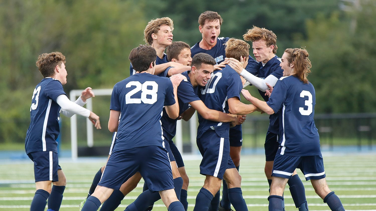 Mark Tricarico is mobbed by teammates after his late goal lifts John Jay over Arlington on Monday.