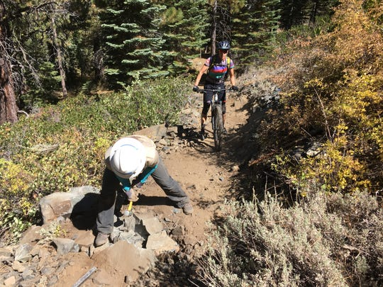 A Tahoe Rim Trail Association volunteer works on the Tahoe Rim Trail as a mountain biker approaches on Sept. 22, 2018.