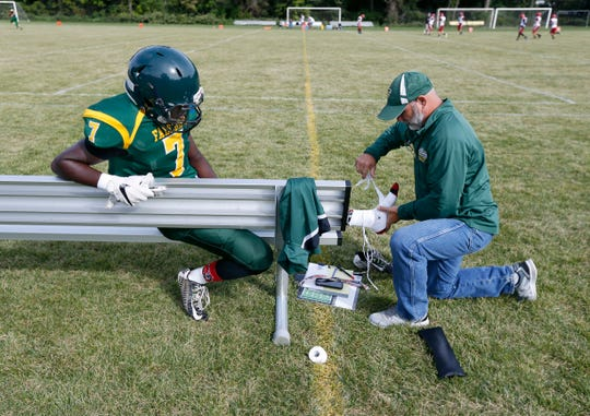 Finney's Maalik Thomas gets his foot bandaged up by coach Joe Marchand before an 8-man football home game against Holley.