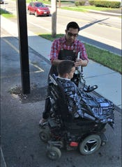 Victor Burgos, a barber at Joe's Upscale Barber Shop in Webster, cuts Devin Hamilton's hair outside the shop in September 2018. The shop has no wheelchair ramp, so Burgos took his tools outside to give Hamilton a haircut.