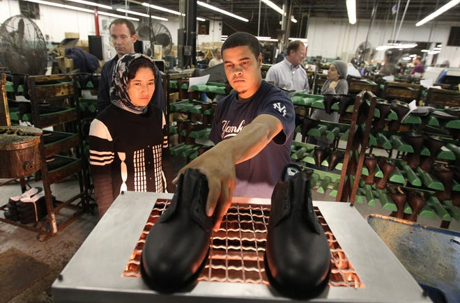 Shahla Akbari, left, an Afghan entrepreneur, learns the shoemaking process from employees at PW Minor Shoe Co., including Jordan Brooks, during a visit to the Batavia shoe manufacturer.