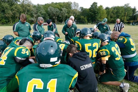 Finney coach Joe Marchand prays with players and staff before an 8-man football home game against Holley.