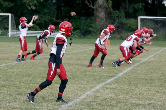 Holley players warm up before an 8-man football at The Charles Finney School.