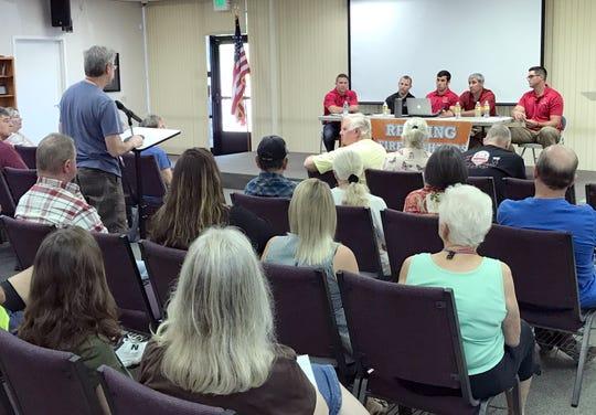 An audience member asks a question for Redding firefighters, from left, Mike Henry, Ryan Nardo, Brett Morris, Matt Oliphant and Joe Hansen during a Carr Fire debriefing Sept. 22.