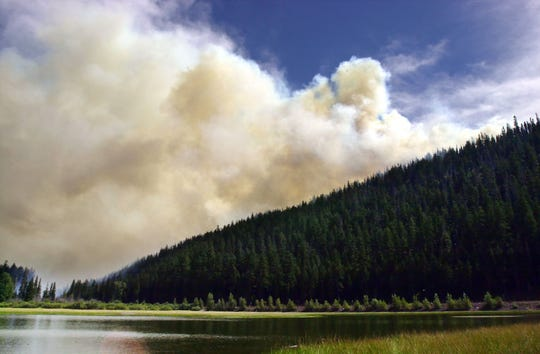 Smoke from the B&B Complex wildfire billows over the ridge above Lost Lake on Aug. 26, 2003.