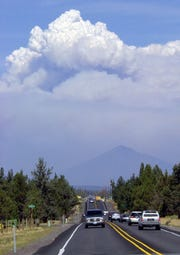 A massive smoke plume from the B&B Complex wildfire shoots skyward over Black Butte as trafffic travels on Highway 20 near Sisters, Ore., Thursday, Aug. 21, 2003.