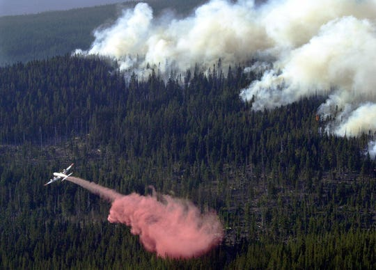 A tanker plane drops retardant in the path of the advancing B&B Complex wildfire near Hoodoo Ski Area in Willamette National Forest west of Sisters, Ore., Monday, Aug. 25, 2003.