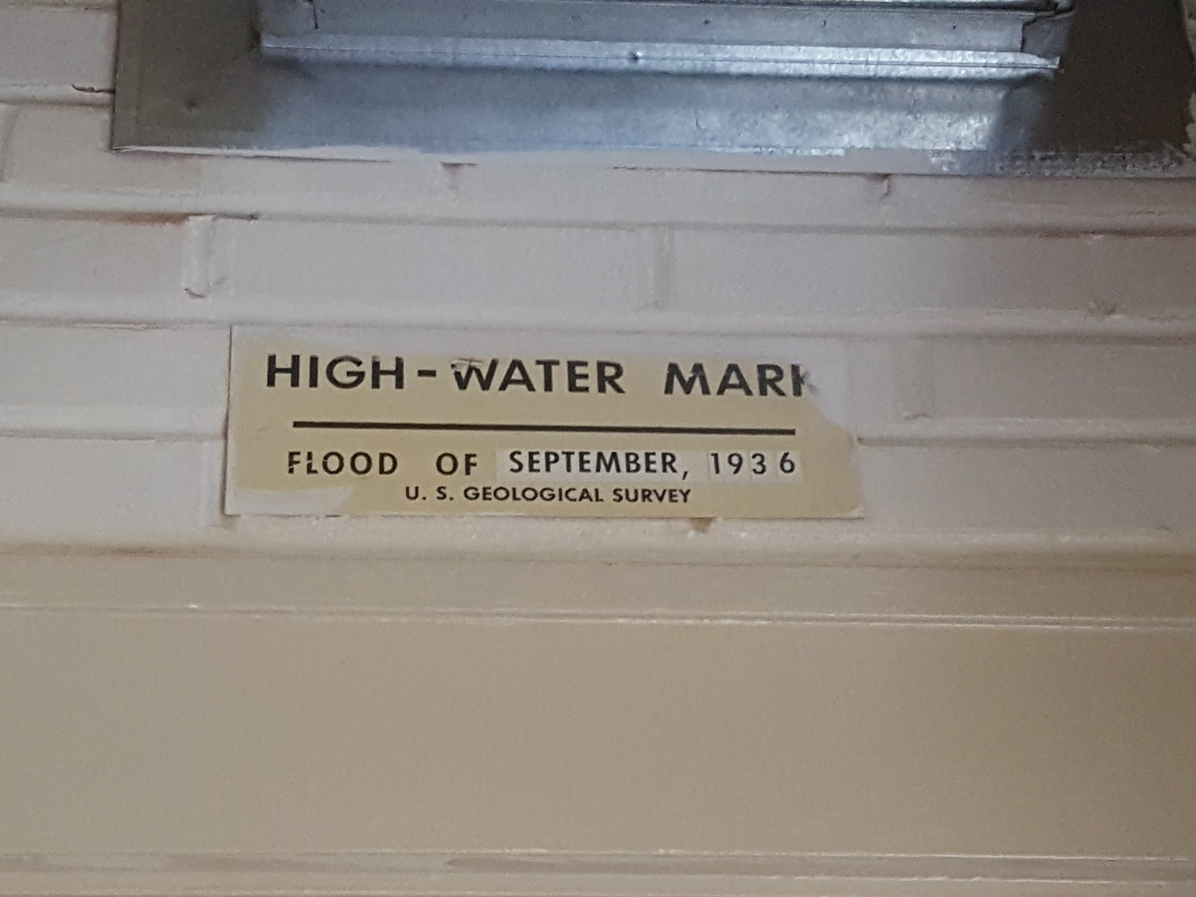 High water mark sign posted above the front door at 200 S Magdalen St, after the flood of September 1936.