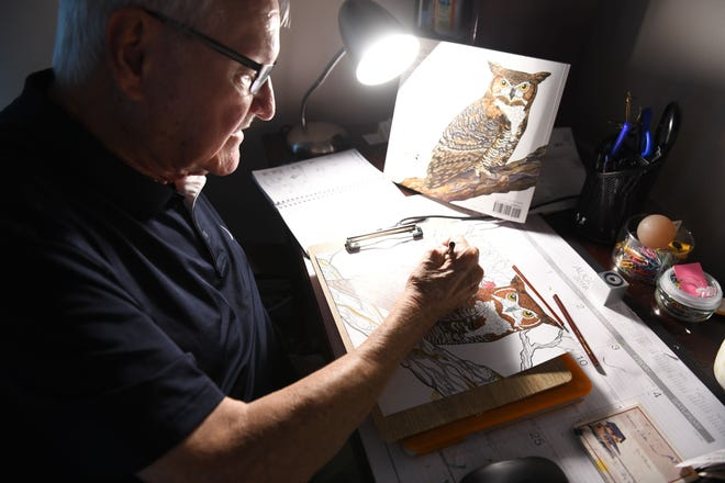 Chuck Ertel works on coloring a horned owl in his home office, which doubles as his studio.