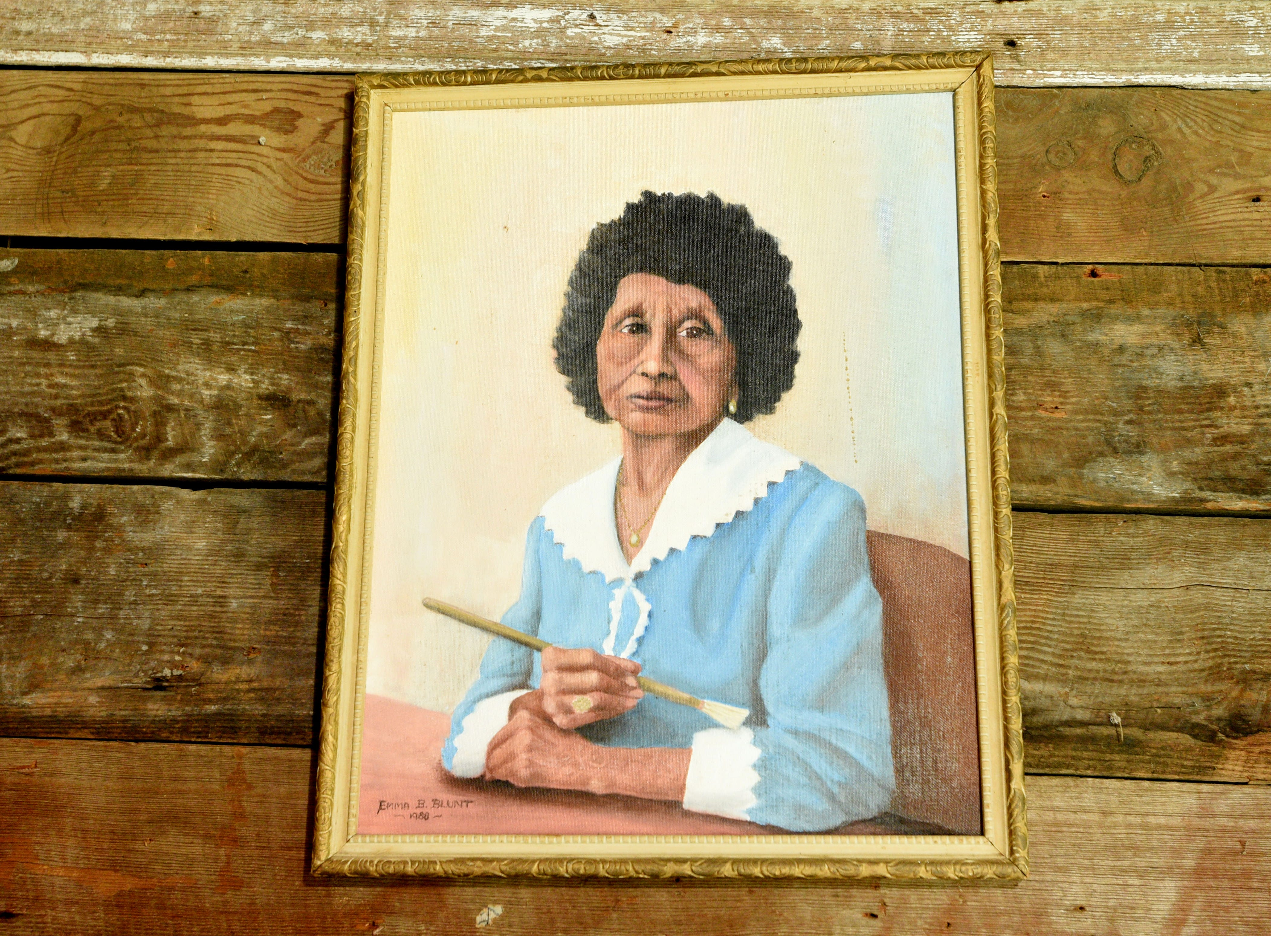 A painting of Clementine Hunter from an unknown artist is on the wall in her house.