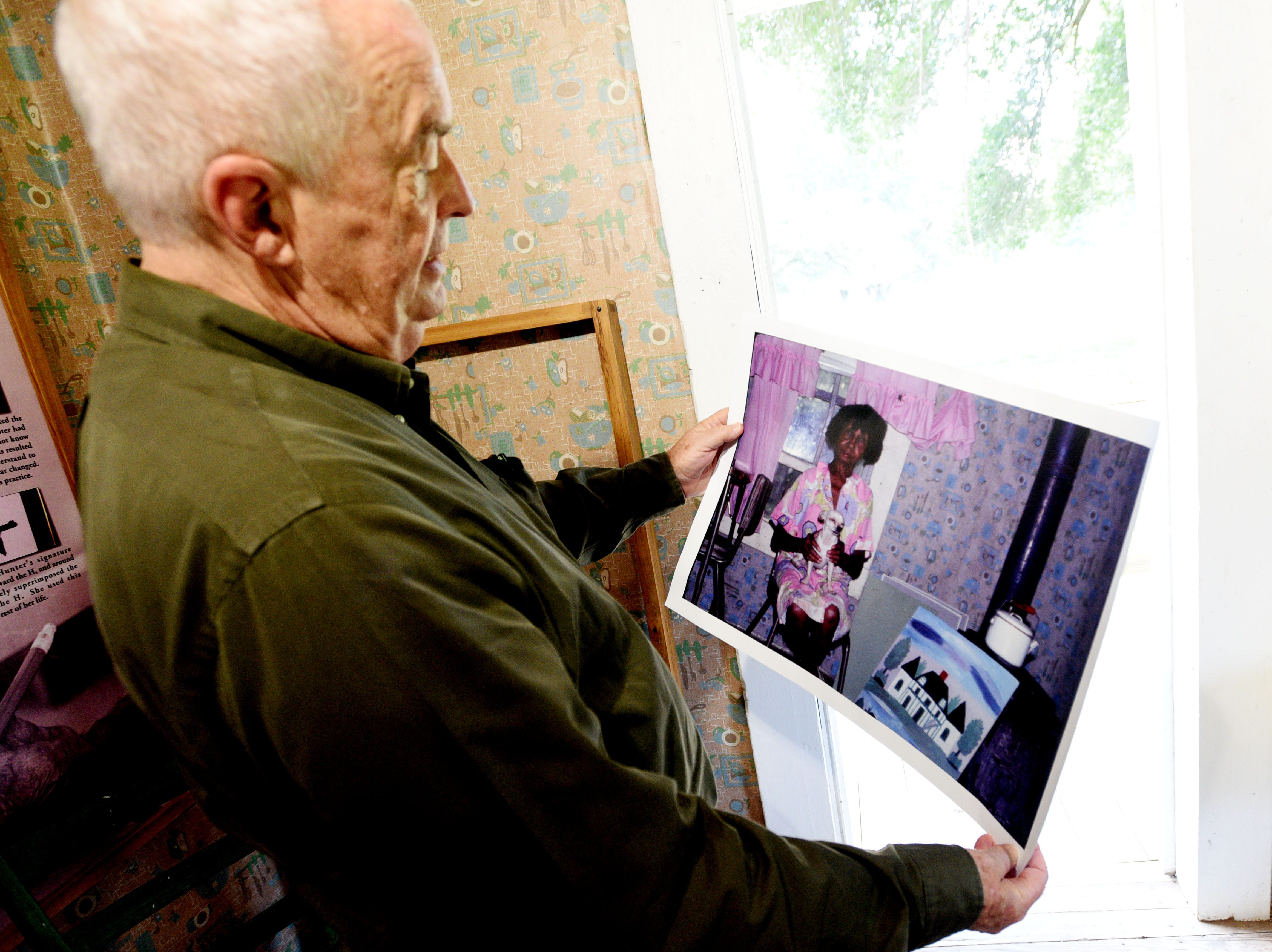 Friend of Clementine Hunter, Tommy Whitehead, looks at a photo he took of her in her house on Melrose Plantation. They used that photo to reproduce the wallpaper in her kitchen.