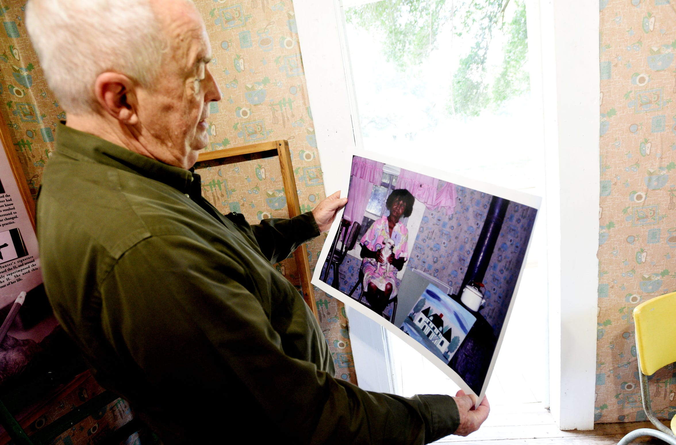 Tommy Whitehead, a friend of Clementine Hunter, looks at a photo he took of her in her house on Melrose Plantation. They used that photo to reproduce the wallpaper in her kitchen.