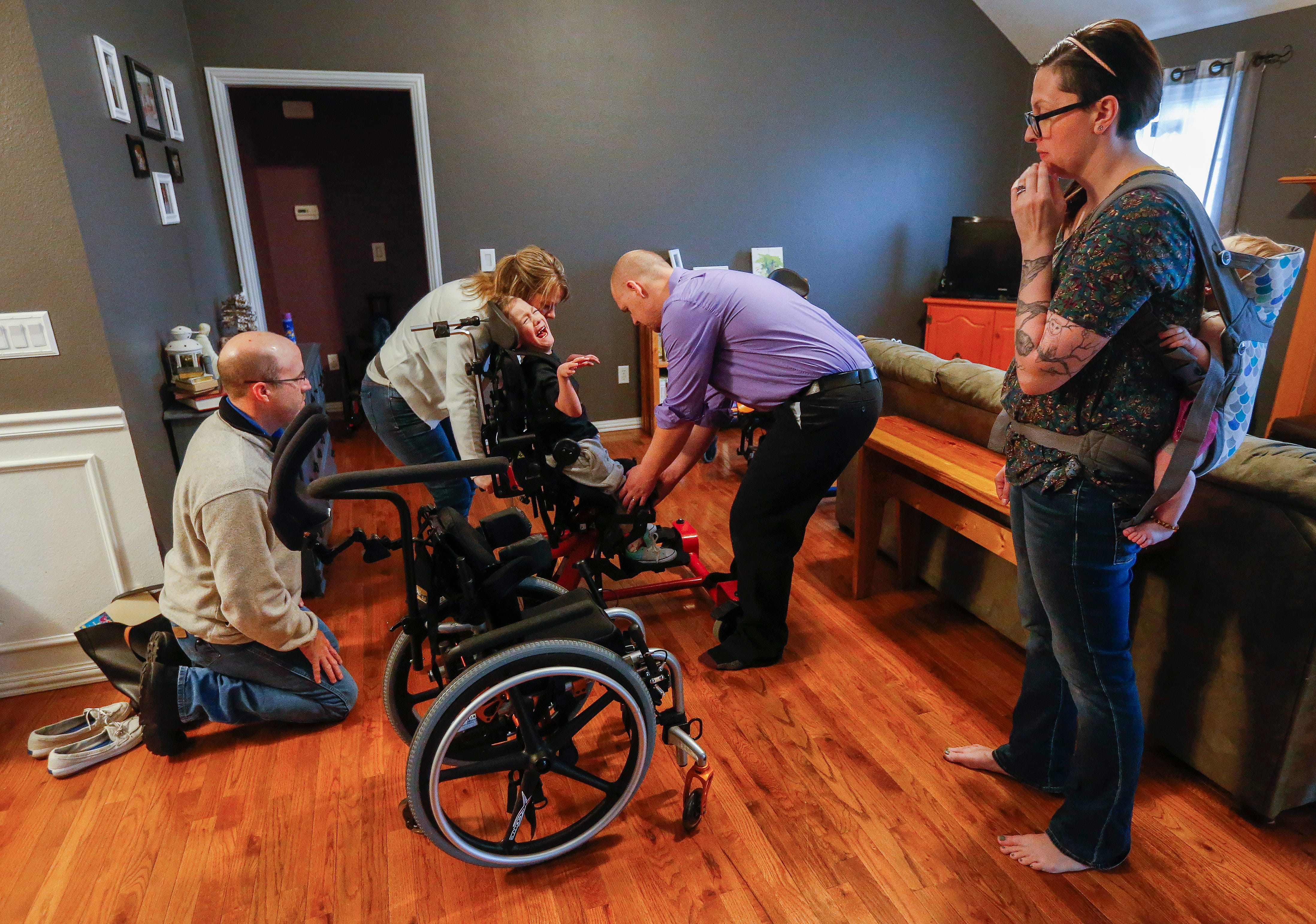Ashley Markum watches her son Ayden Markum, 5, as Sara Rozell, a physical therapy assistant, and Josh Tinker, of Alliance Rehab & Medical Equipment, gets help from Chris Markum while working on Ayden's chair at the Markum's home in Rogersville on Monday, March 26, 2018.