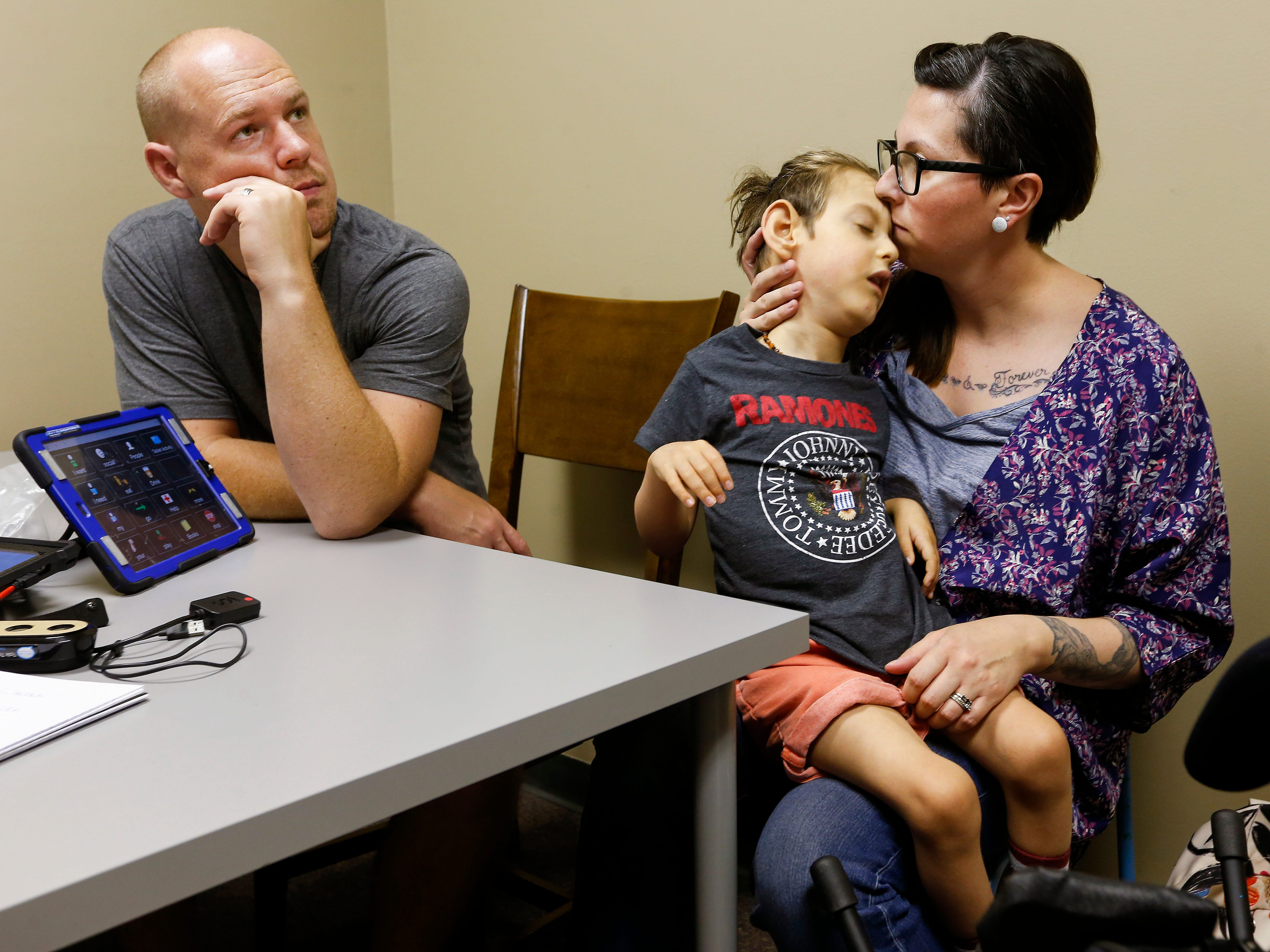 Chris and Ashley Markum along with speech therapist Amber Harlan meet with Allyson Beary about getting Ayden an eyegaze communication device at TheraCare in Springfield.