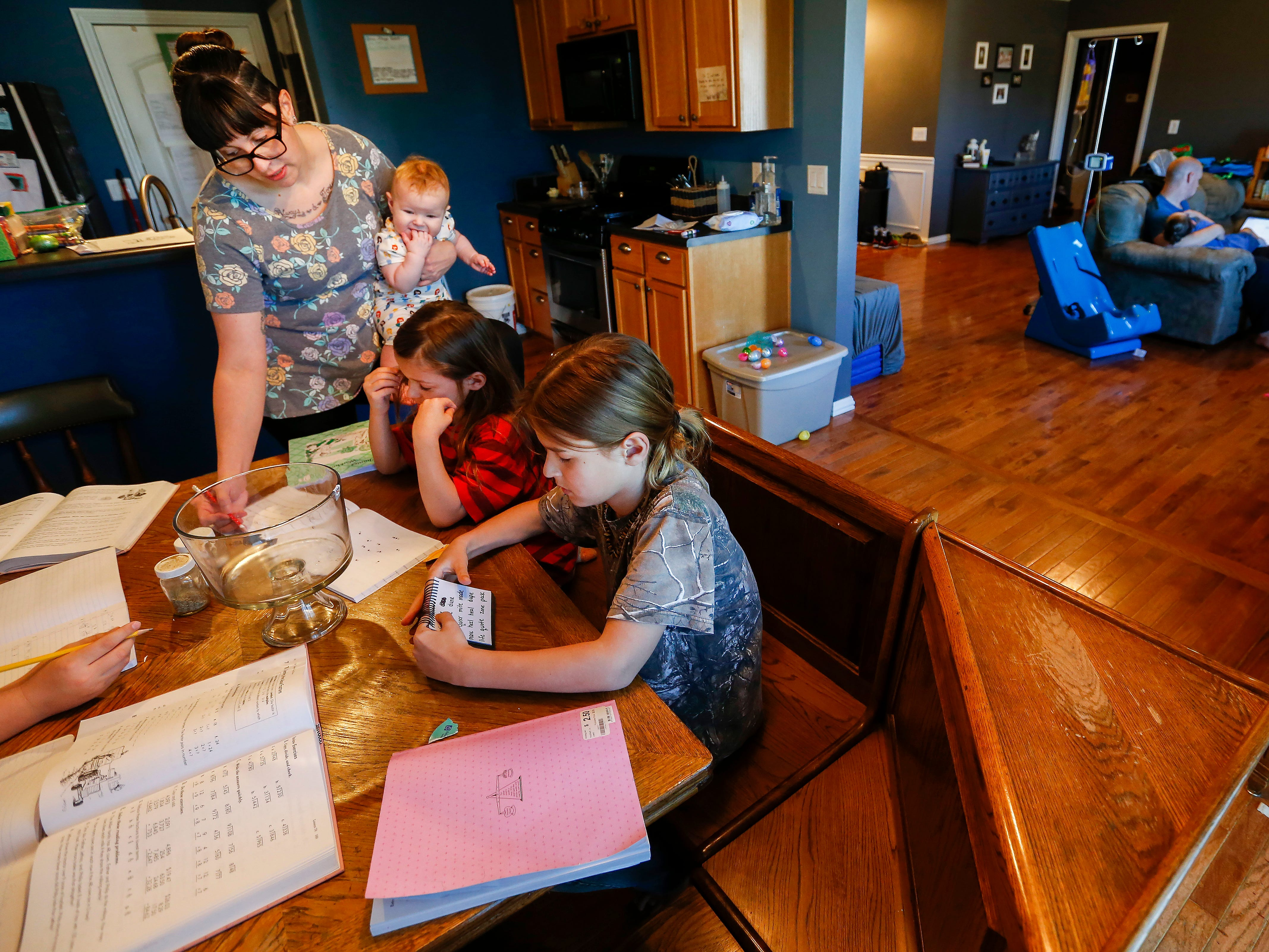 Ashley Markum holds her daughter Letty, 7-months, while helping Asher, 6, and Asa, 8, with their school work at their home in Rogersville on Friday, April 27, 2018. Chris Markum sits on the couch i the other room holding his son Ayden, 5, while researching his insurance coverage for an eyegaze communication device for Ayden.