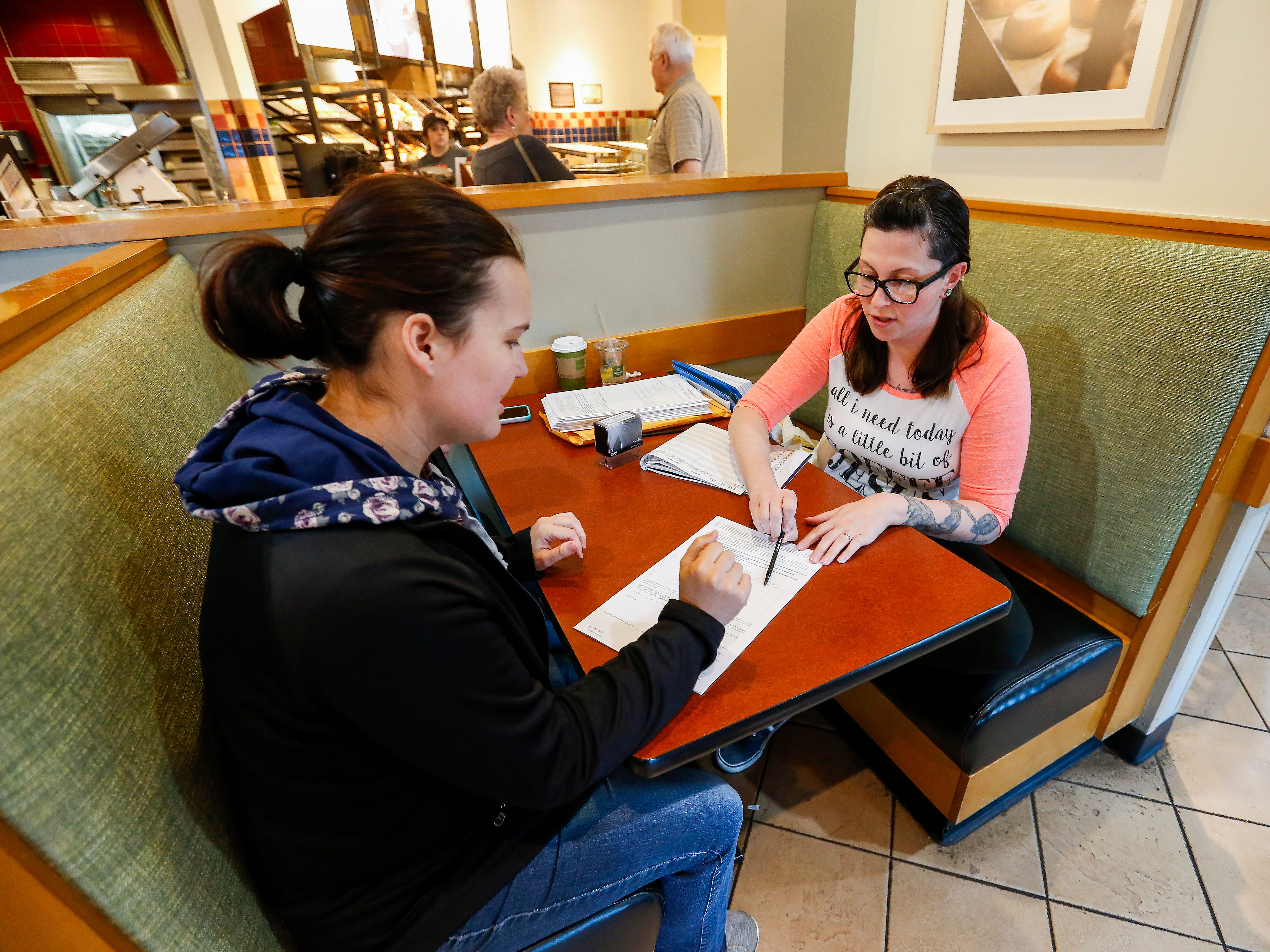 Ashley Markum shows Chelsea Joy, of Elkland, where to sign the petition to get the New Approach Missouri medical marijuana amendment on the November ballot at Panera on Saturday, April 28, 2018.