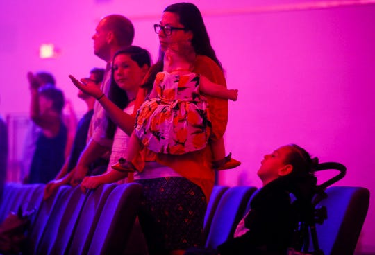 Ashely Markum, center, raises her hand in prayer while holding her daughter Letty during services at Venture Church on Sunday, Aug. 19, 2018. Standing with her are her daughter Eliza, 11, husband Chris, son Isaiah, 12, and seated is her son Ayden, 5.