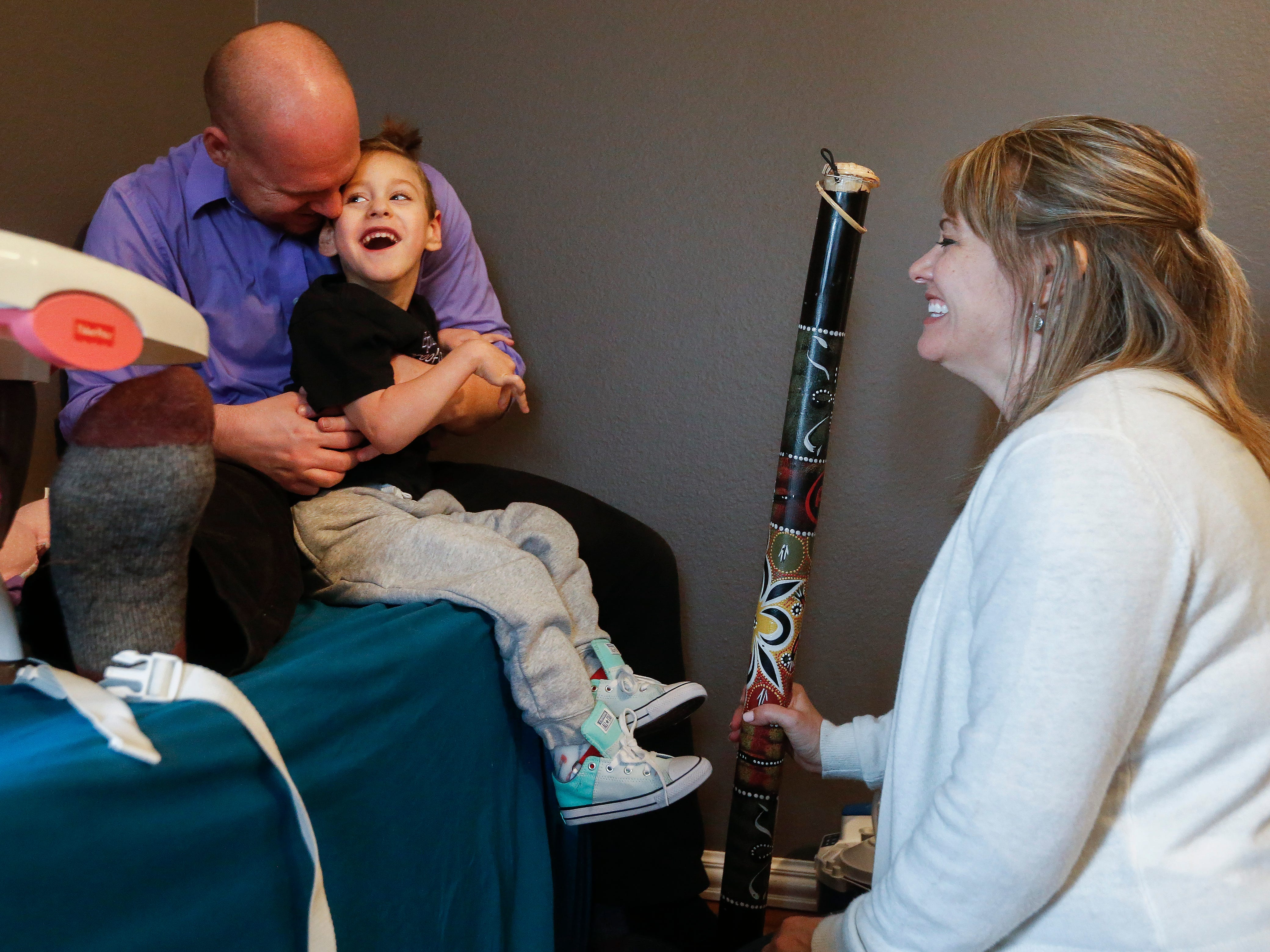 Ayden Markum, 5, laughs with his dad Chris Markum and physical therapy assistant Sara Rozell as the rain stick makes noise at the Markum's home in  Rogersville on Monday, March 26, 2018.