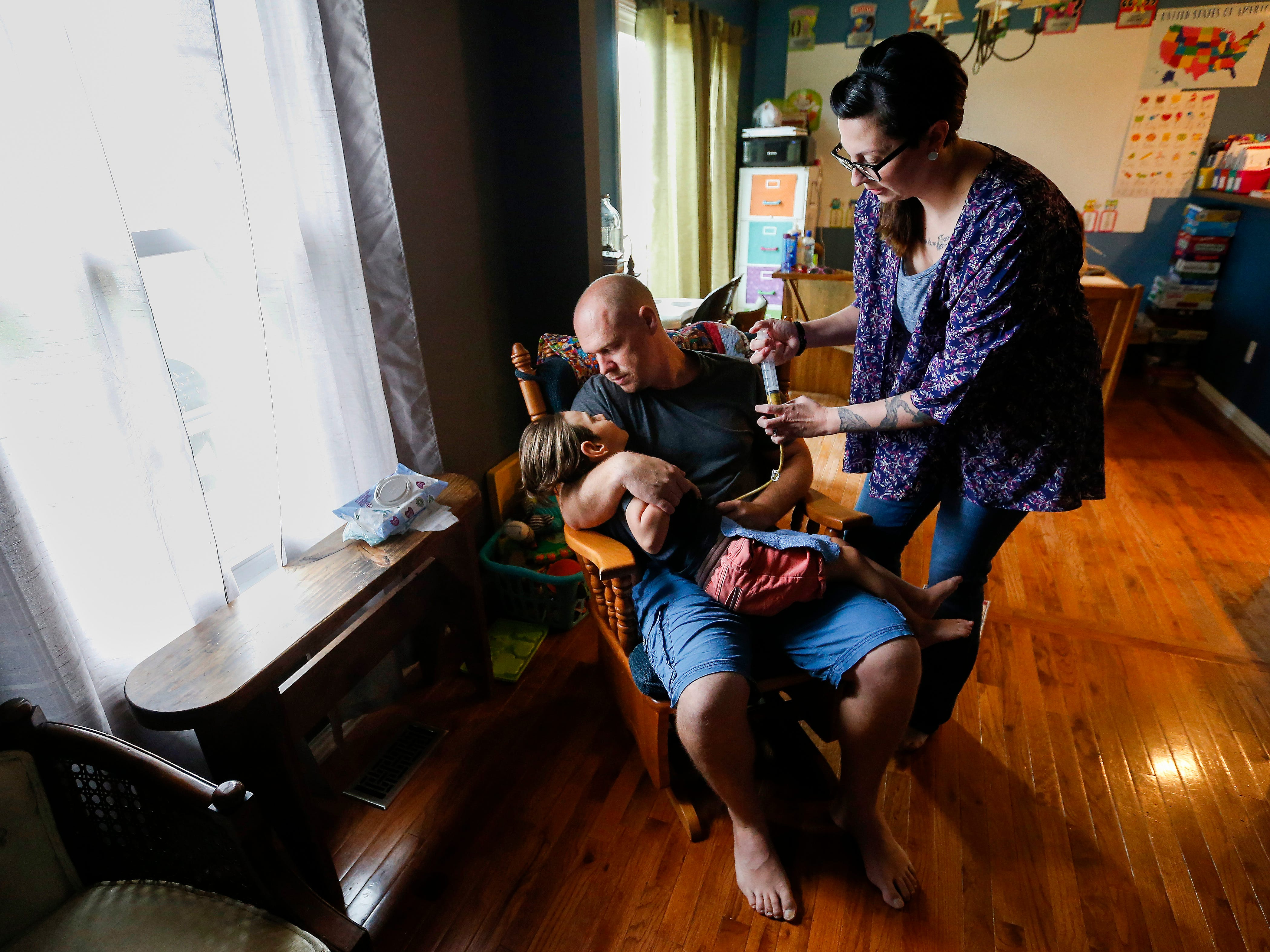 Ashley Markum injects food into her son Ayden's feeding tube as he sits on his dad Chris Markum's lap at their home in Rogersville on June 12, 2018.