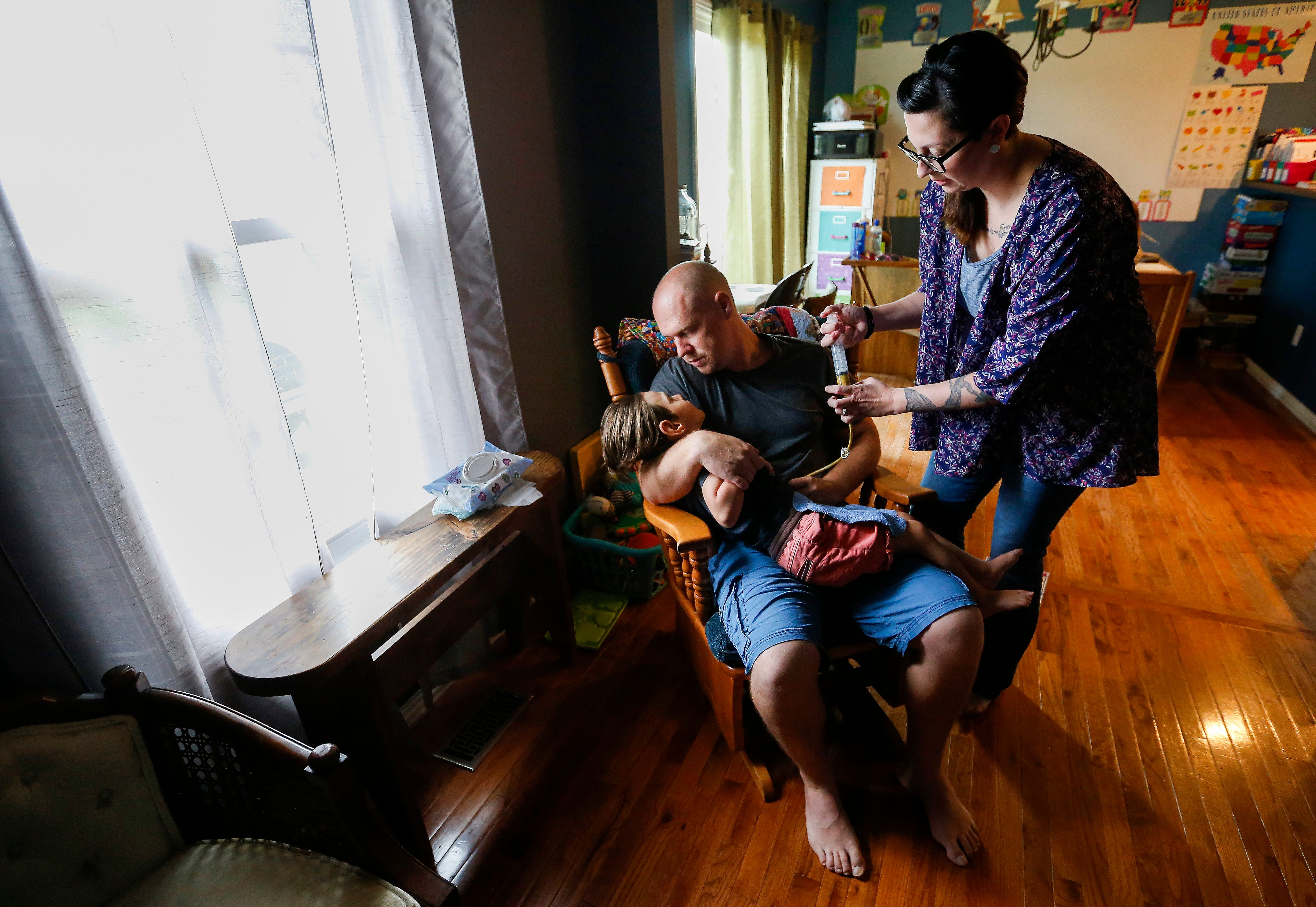 Ashley Markum Injects Food Into Her Son Aydens Feeding Tube As He Sits On His Dad