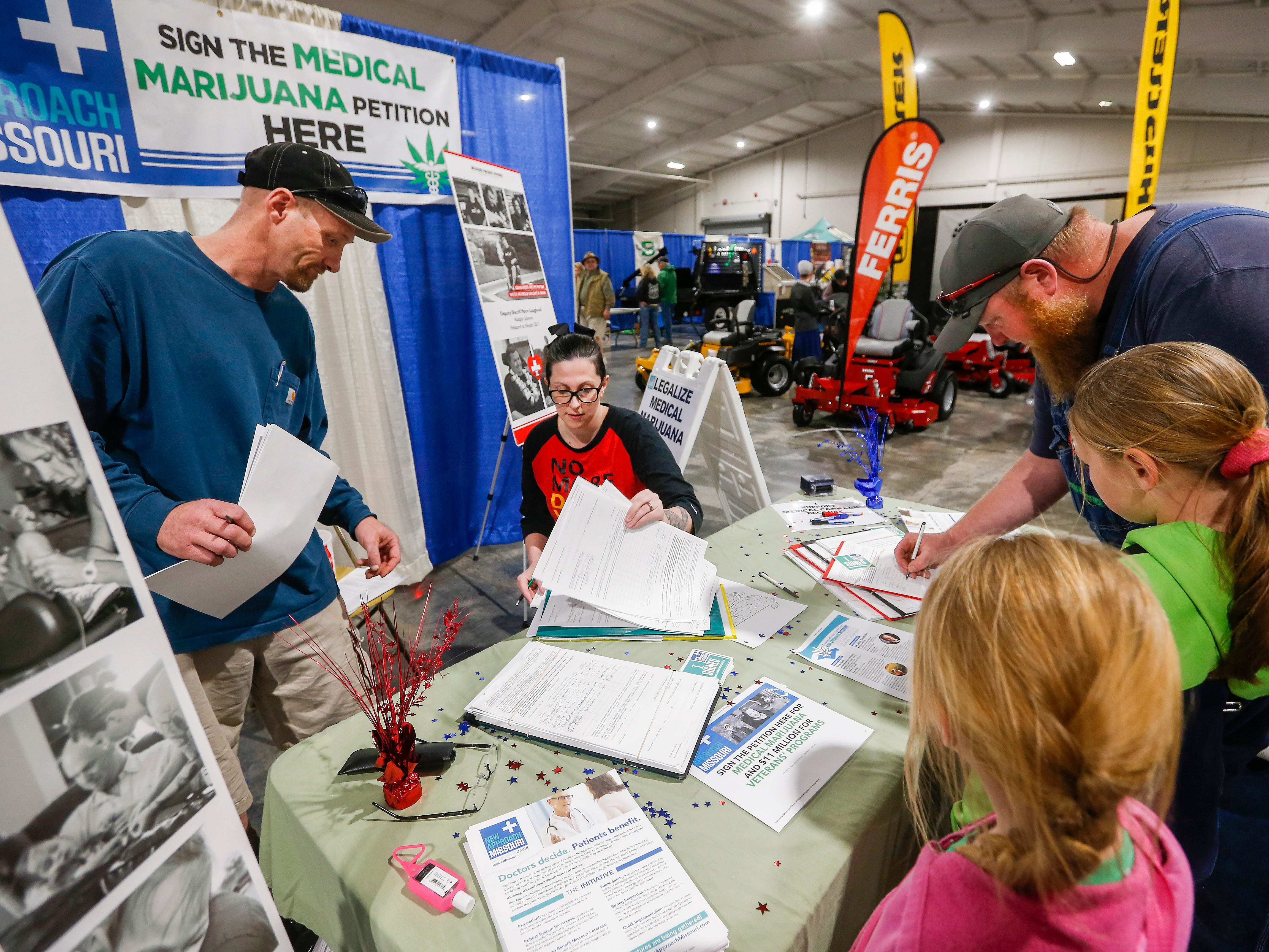 Ashley Markum and Josh Loftis notarize signatures as Matthew Dickinson, of Seymour, signs the petition for New Approach Missouri to get the medical marijuana amendment on the November ballot as his daughters Lexi Dickinson, 9, center, and Kassitie Dickinson, 6, watch during the Ozark Spring Roundup at the Ozark Empire Fairgrounds on Saturday, March 24, 2018.