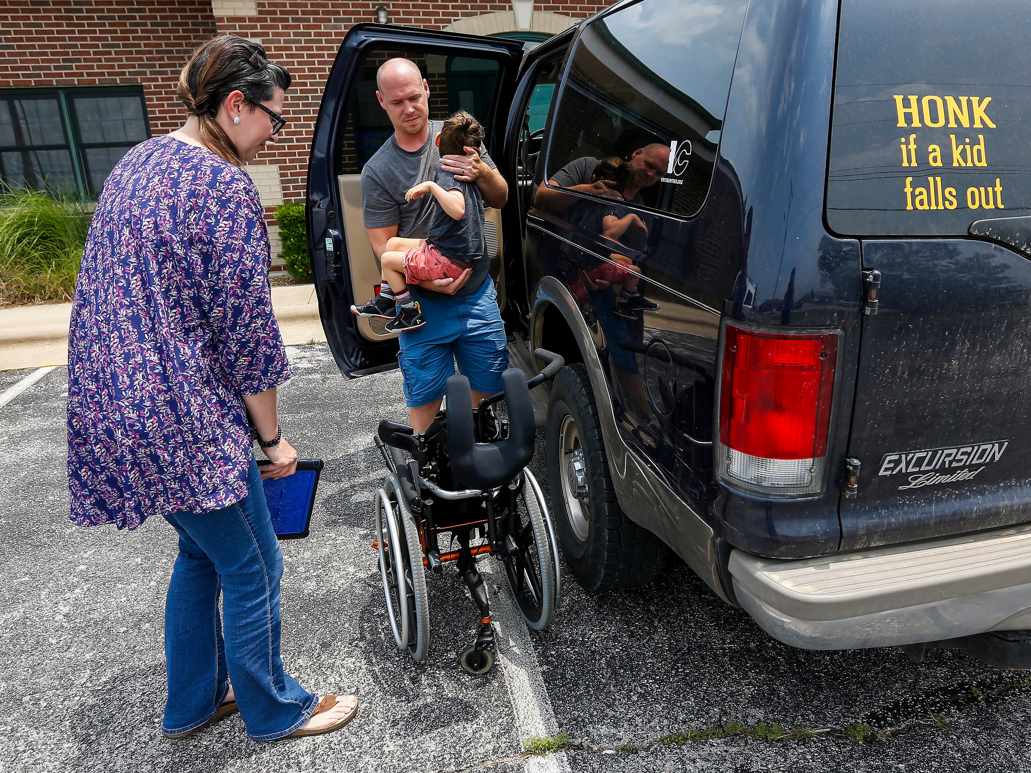 Chris and Ashley Markum lift their son Ayden out of the car and into his wheelchair outside of TheraCare in Springfield on Tuesday, June 12, 2018.
