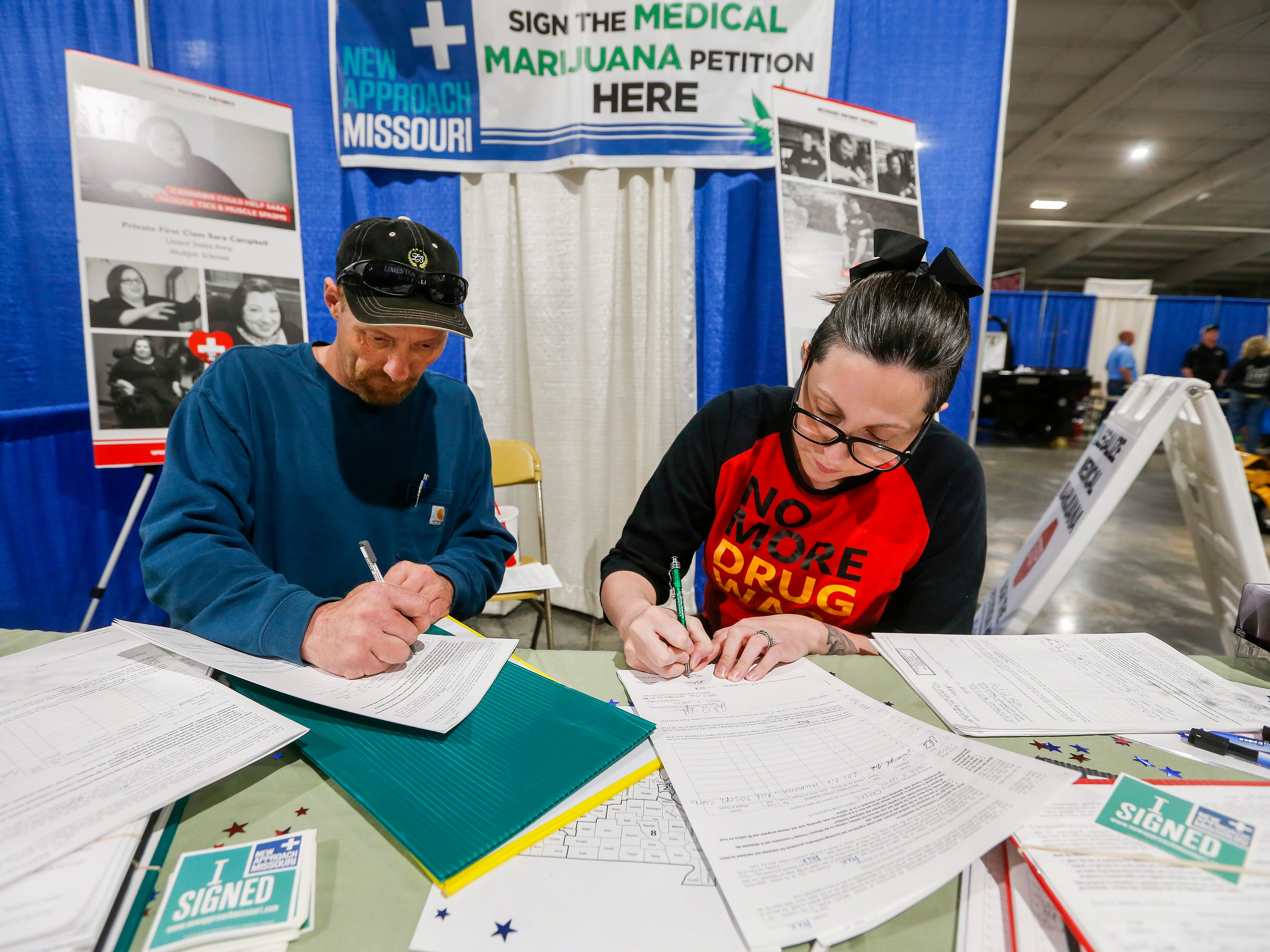 Ashley Markum and Josh Loftis notarize signatures for New Approach Missouri to get the medical marijuana amendment on the November ballot during the Ozark Spring Roundup at the Ozark Empire Fairgrounds on Saturday, March 24, 2018.