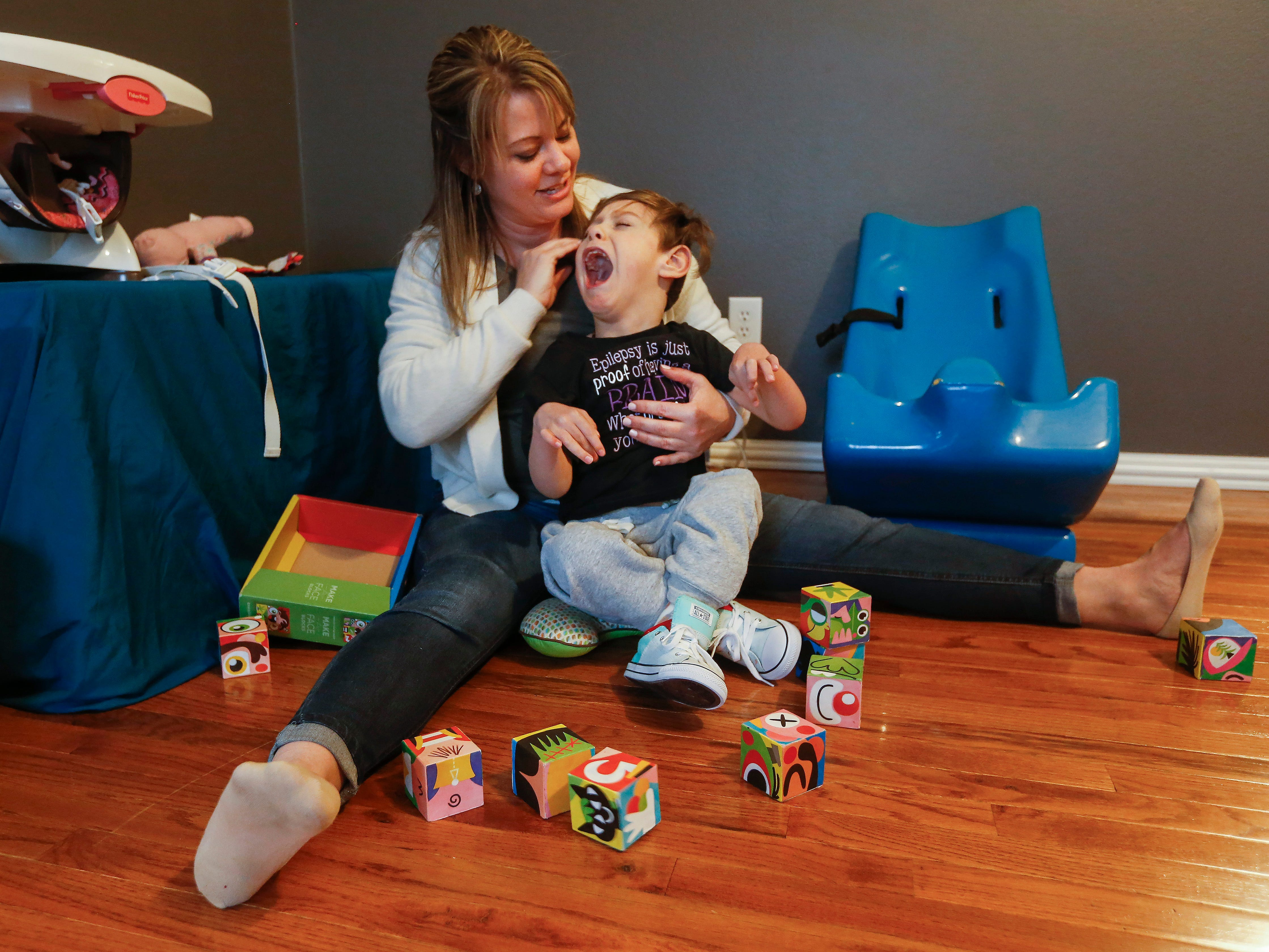 Sara Rozell, a physical therapy assistant, works with Ayden Markum, 5, at the Markum's home in Rogersville on Monday, March 26, 2018.