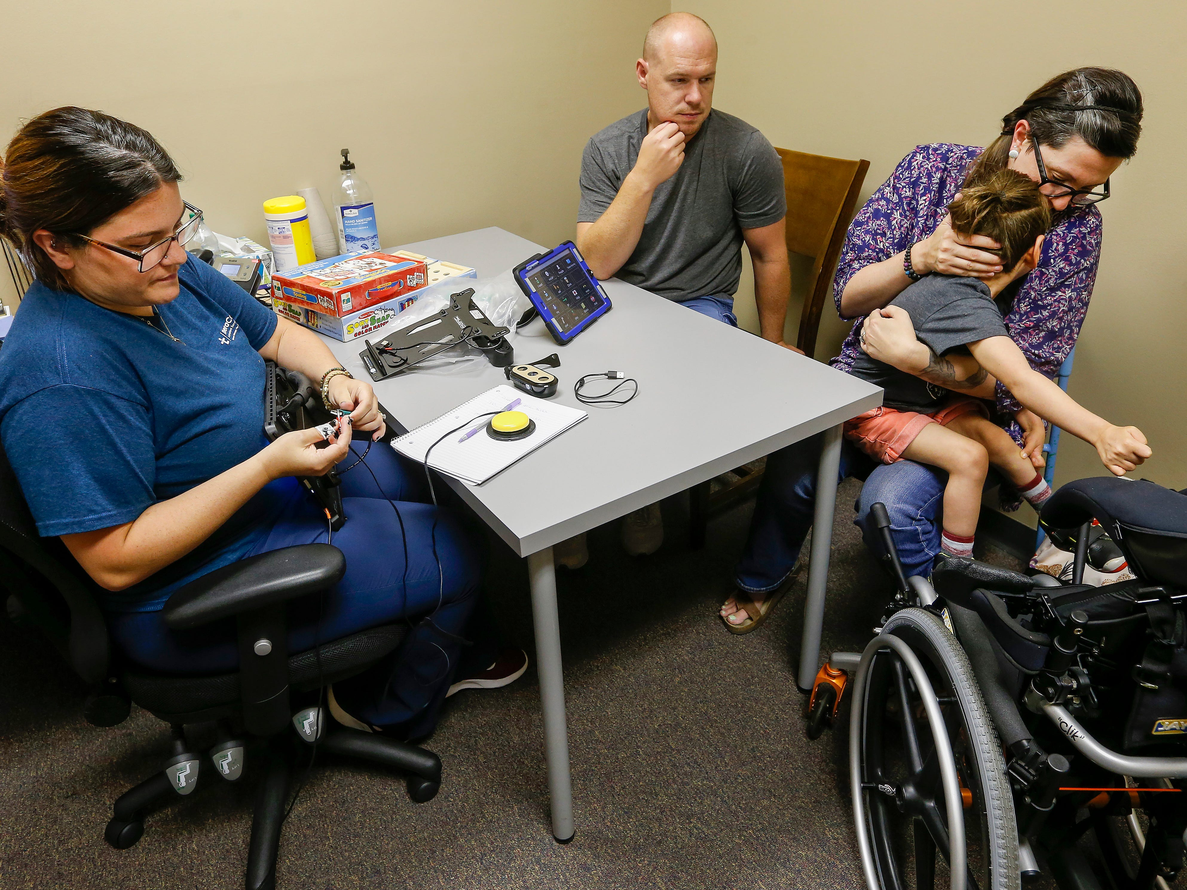 Chris watches as Ashley Markum holds Ayden Markum, 5, as he has a seizure while meeting with Allyson Beary about getting an eyegaze communication device at TheraCare in Springfield on Tuesday, June 12, 2018.