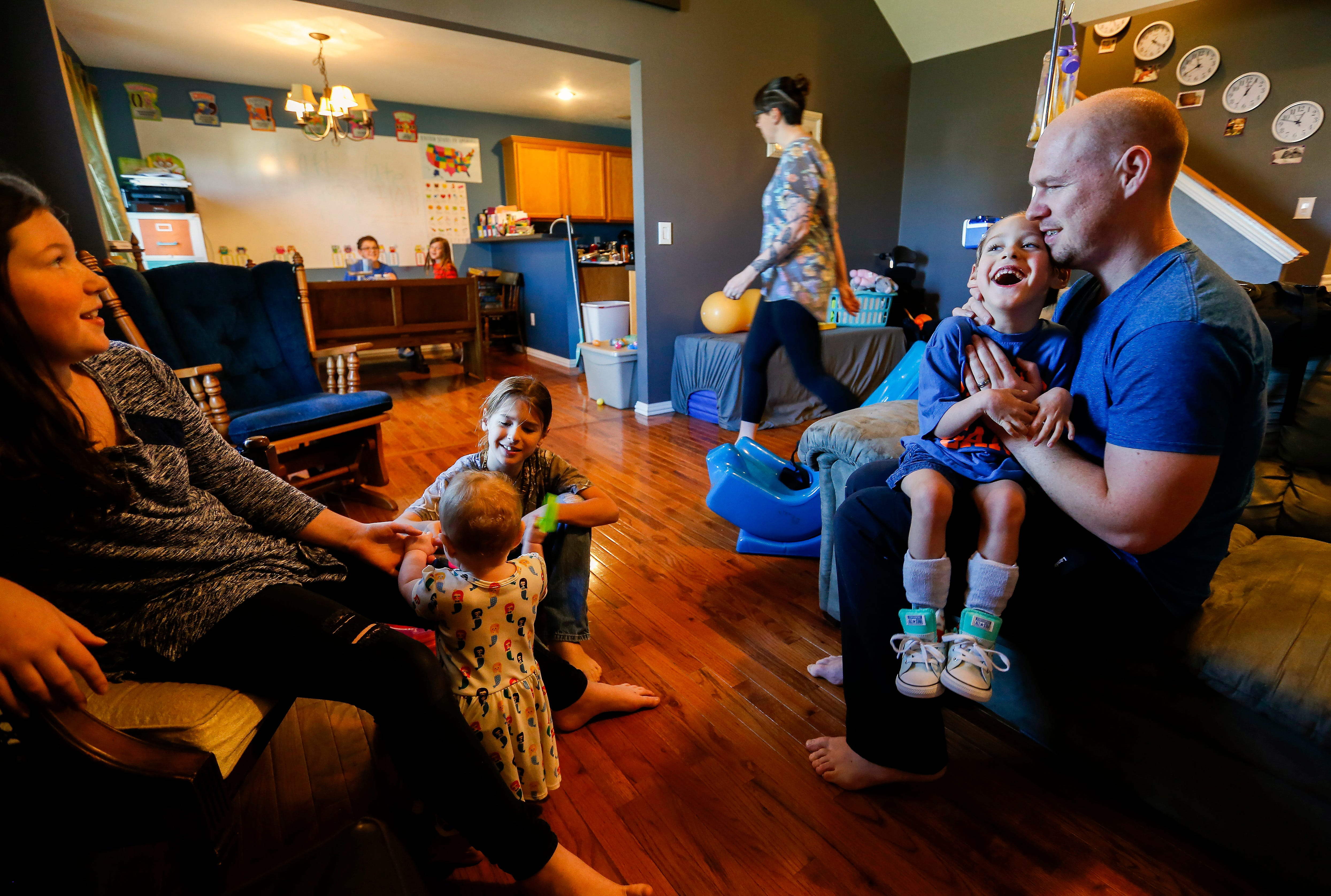 Ayden Marum laughs as he sits on his dad Chris Markum's lap while talking to, from right, Eliza, 11, Letty, 7-months, and Asa, 8, in the living room of their home in Rogersville on Friday, April 27, 2018.