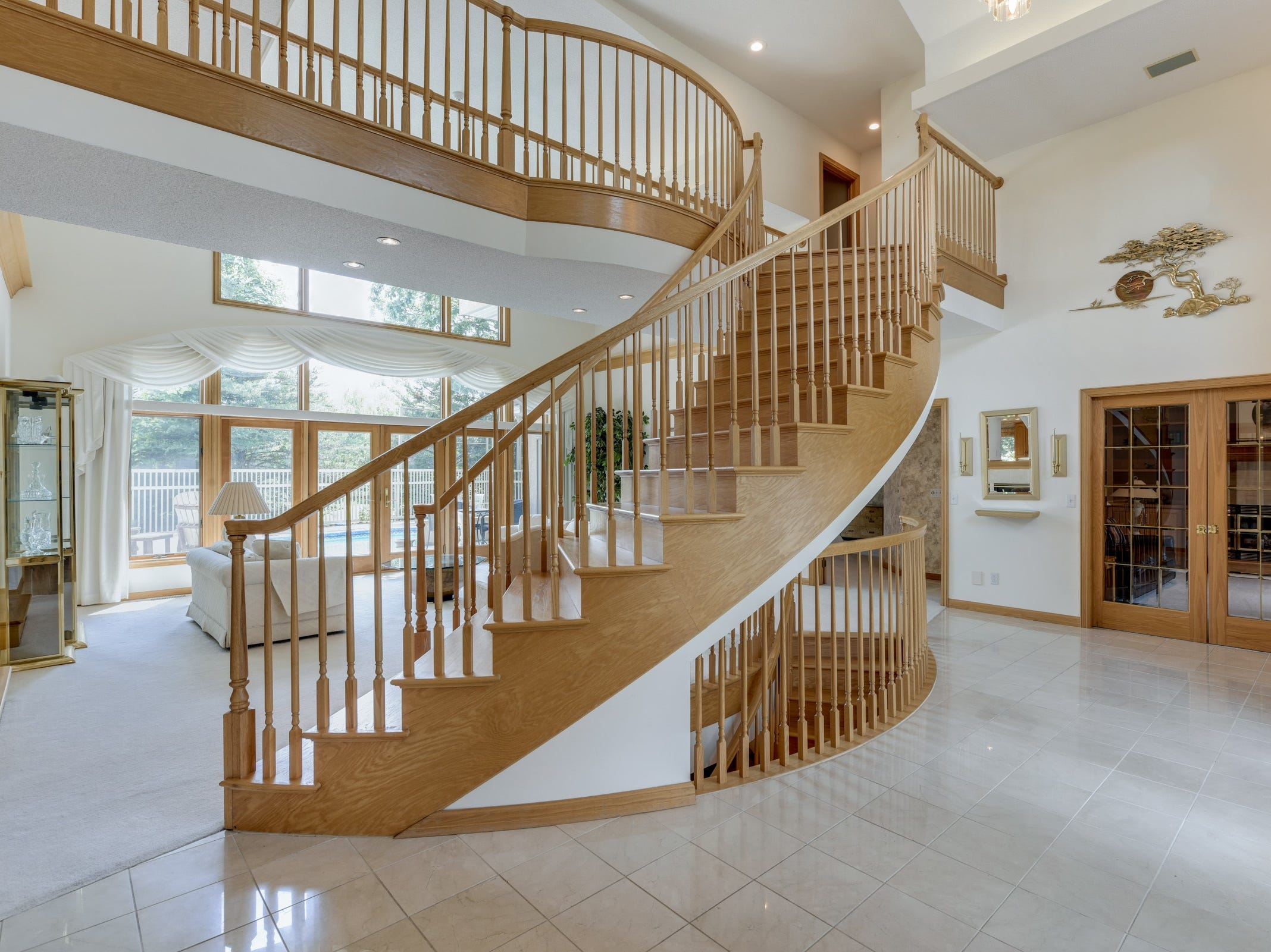 Inside, the windows allow light to stream into the house and highlight the dramatic winding staircase which leads to an upper level catwalk.