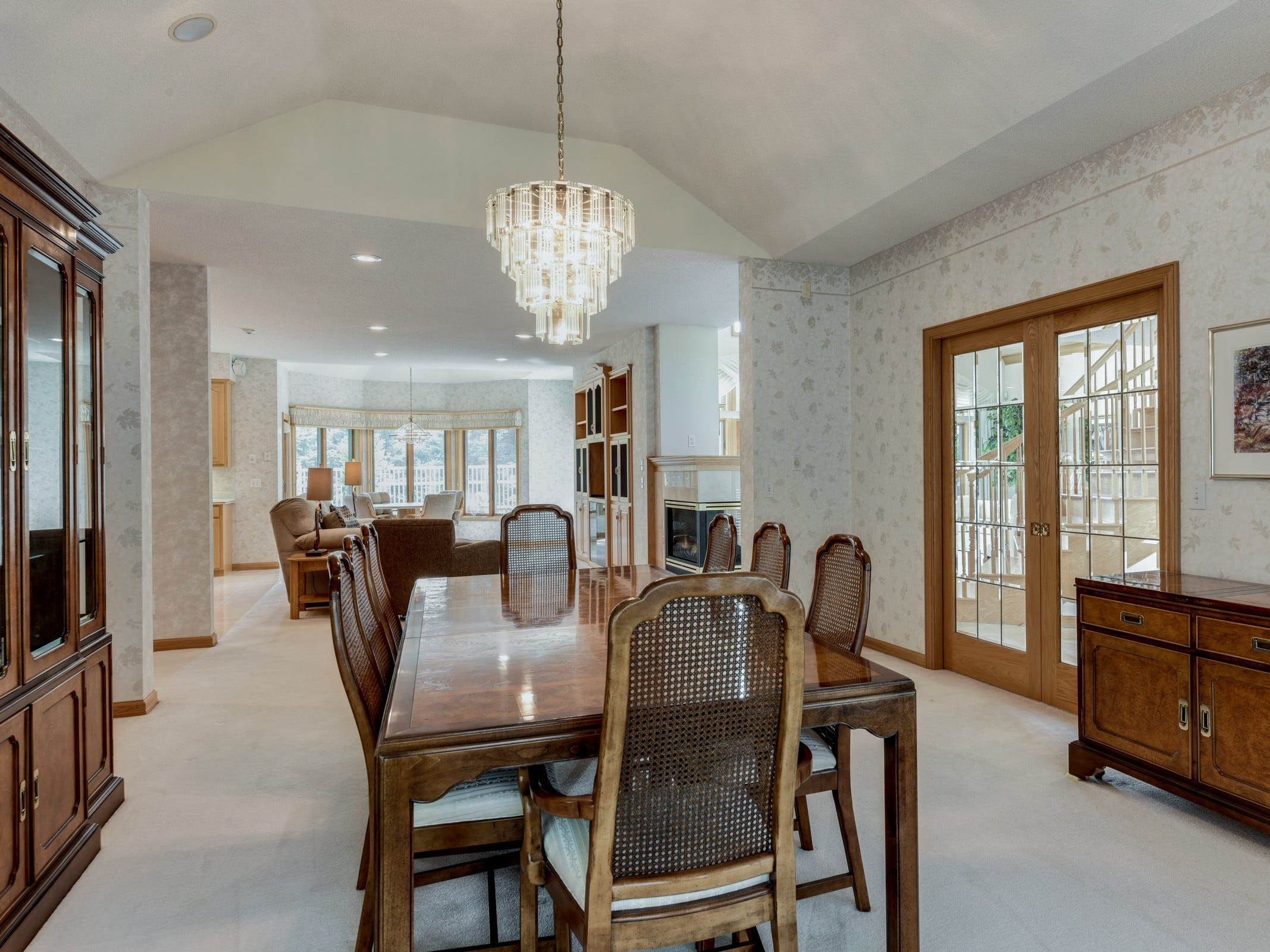 The formal dining room can be accessed via French doors from the entryway and features a crystal chandelier as well as a rounded bay window.