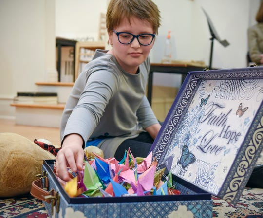 Eliana Szabo, 11, looks at the paper cranes Cecilia Maus-Conn folded and is selling as a fundraiser for her Sept. 20, 2018, at Wirth Center for the Performing Arts.