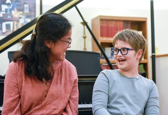 Cecilia Maus-Conn, 16, and Eliana Szabo, 11, laugh and talk as they sit at the piano Thursday, Sept. 20, at Wirth Center for the Performing Arts where they met. Szabo had an arteriovenous malformation rupture and spent 87 nights in the Mayo Clinic in Rochester. Maus-Conn has started a nonprofit and is folding 1000 paper cranes for Eliana as a fundraiser.