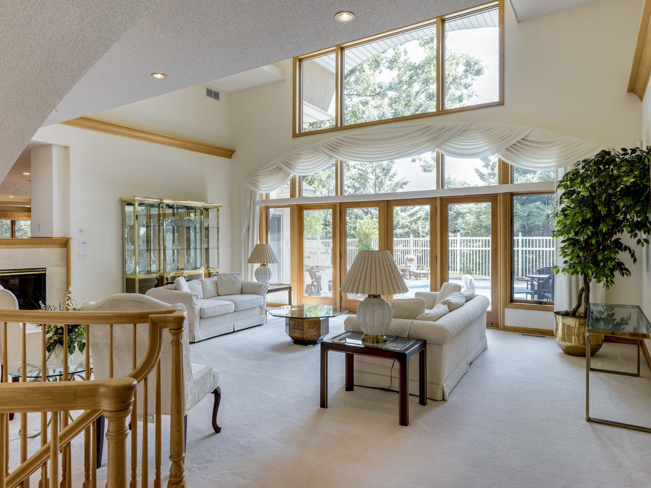 Just beyond the staircase sits the living room with its two-story ceilings and wall-to-wall, floor-to-ceiling windows.