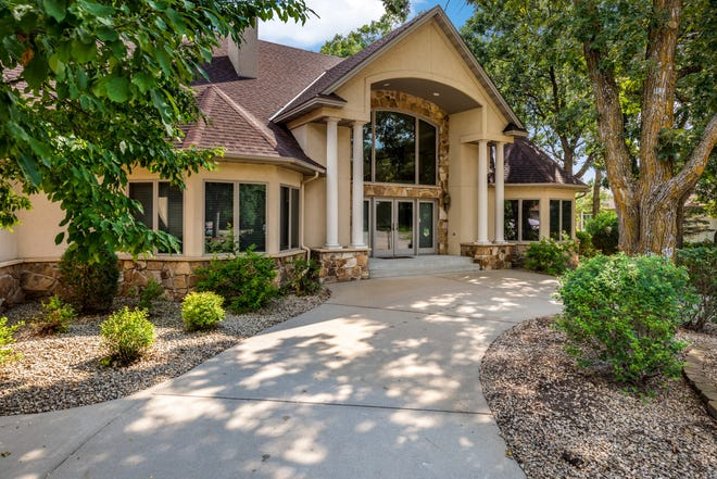 This nearly 7,000-square-foot home welcomes guests with a grand front entry complete with double front doors nestled under a huge picture window framed by pillars and natural stone.