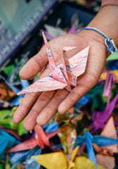 Cecilia Maus-Conn, 16, is folding 1,000 colorful paper cranes as a fundraiser for her friend Eliana Szabo shown Thursday, Sept. 20, at Wirth Center for the Performing Arts.