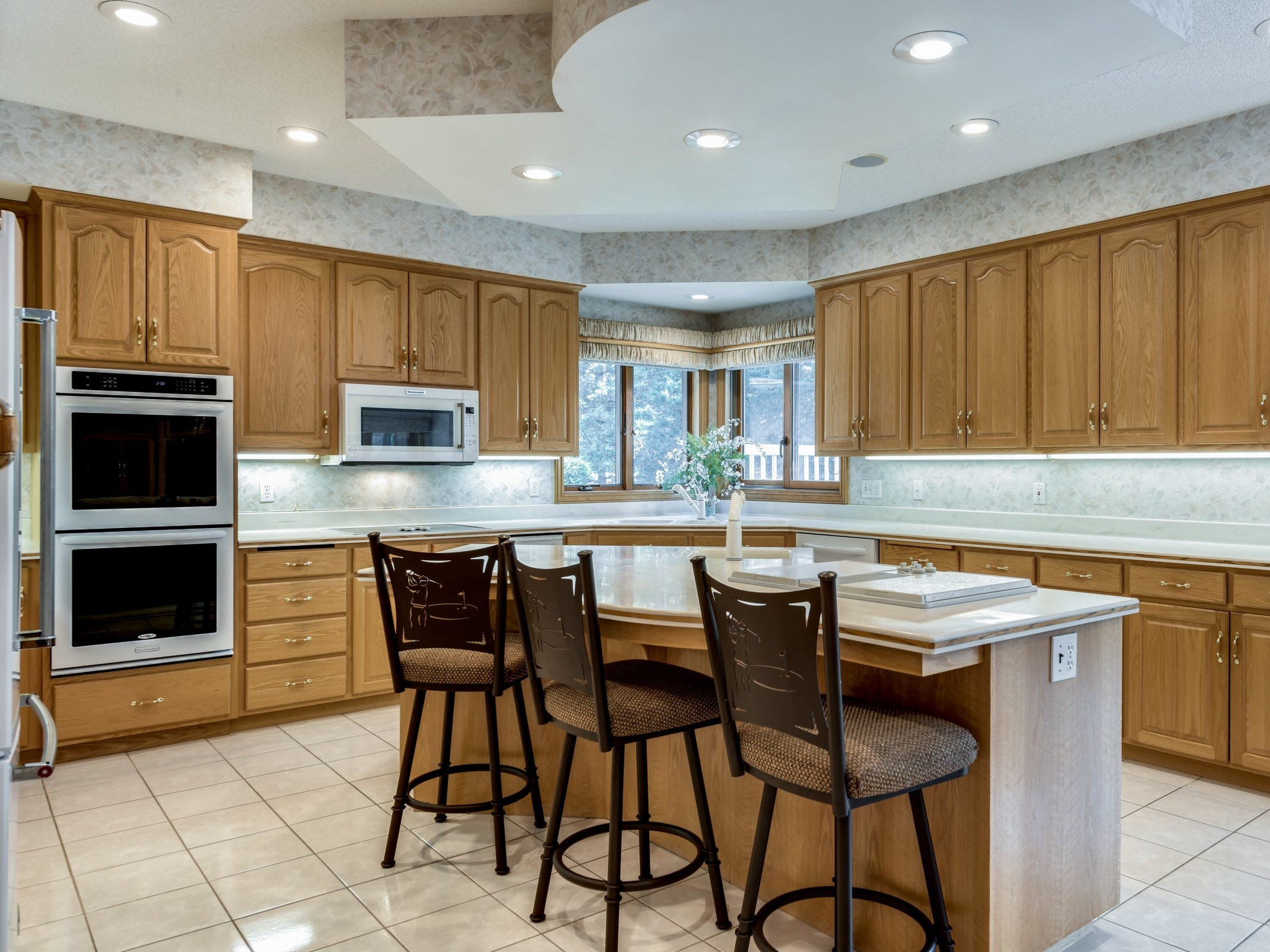 The kitchen features a large center island with a cooktop, prep sink and space for sitting.