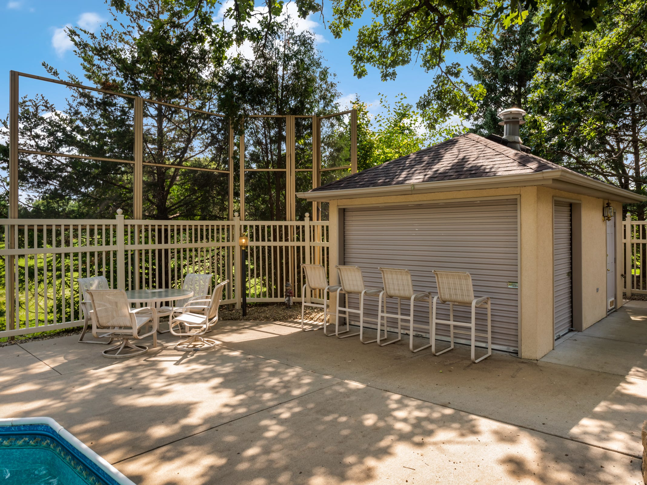 The outdoor space has a pool house featuring a ¾ bath as well as a wet bar and a built-in grill.
