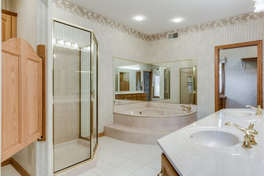 The master suite is complete with an en suite with a round marble jetted tub, a double vanity and a stand-alone shower.