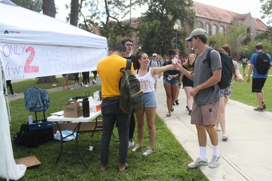 Madison Resnick, an FSU freshman, hands out National Voter Registration Day stickers to a student passing by a tent for the Florida New Voters Project in Landis Green on the FSU campus Tuesday, Sept. 25, 2018. Along with stickers, the volunteers handed out candy, donuts and coffee to attract students to the tent.