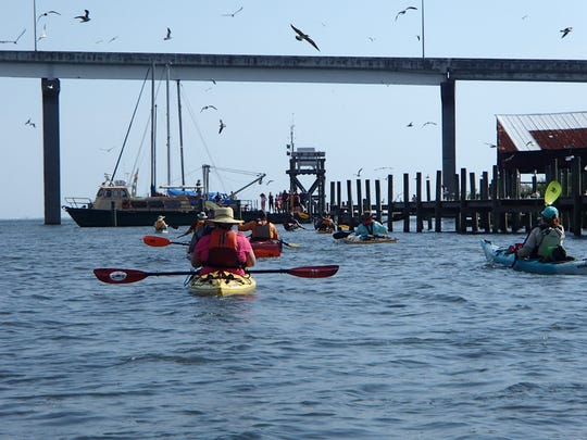 Paddlers approach the bridge between the city of Apalachicola and East Point near the mouth of the Apalachicola Bay at the Gulf of Mexico