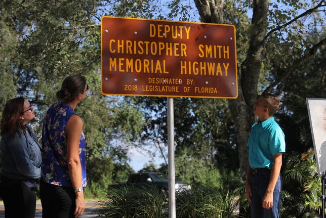 Chris Smith's widow Erika Smith, his daughter Gabrielle Smith and son Hunter PIttman, unveil a memorial sign along U.S. Highway 90 spanning Leon and Jefferson counties on Tuesday.