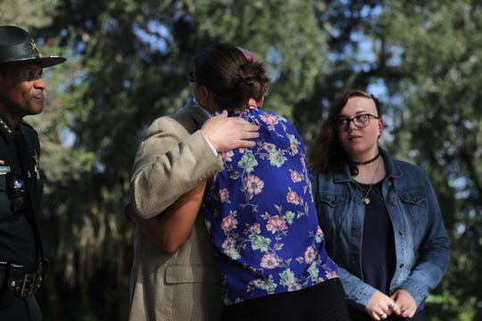 Chris Smith's widow Erika Smith hugs Sen. Bill Montford following the unveiling of a U.S. Highway 90 marker memorializing the slain deputy.