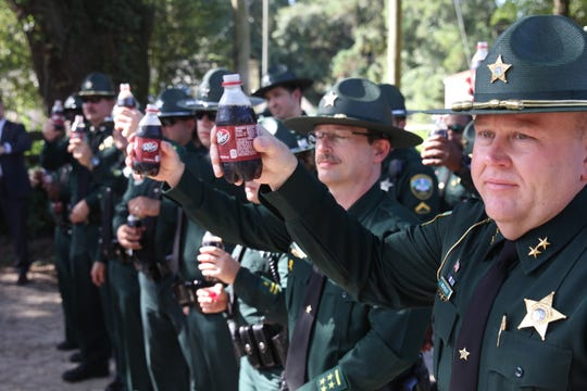 Members of the Leon County Sheriff's Office toast, with Dr. Pepper, to slain colleague Chris Smith. Smith was known to start his shifts with a Dr. Pepper.